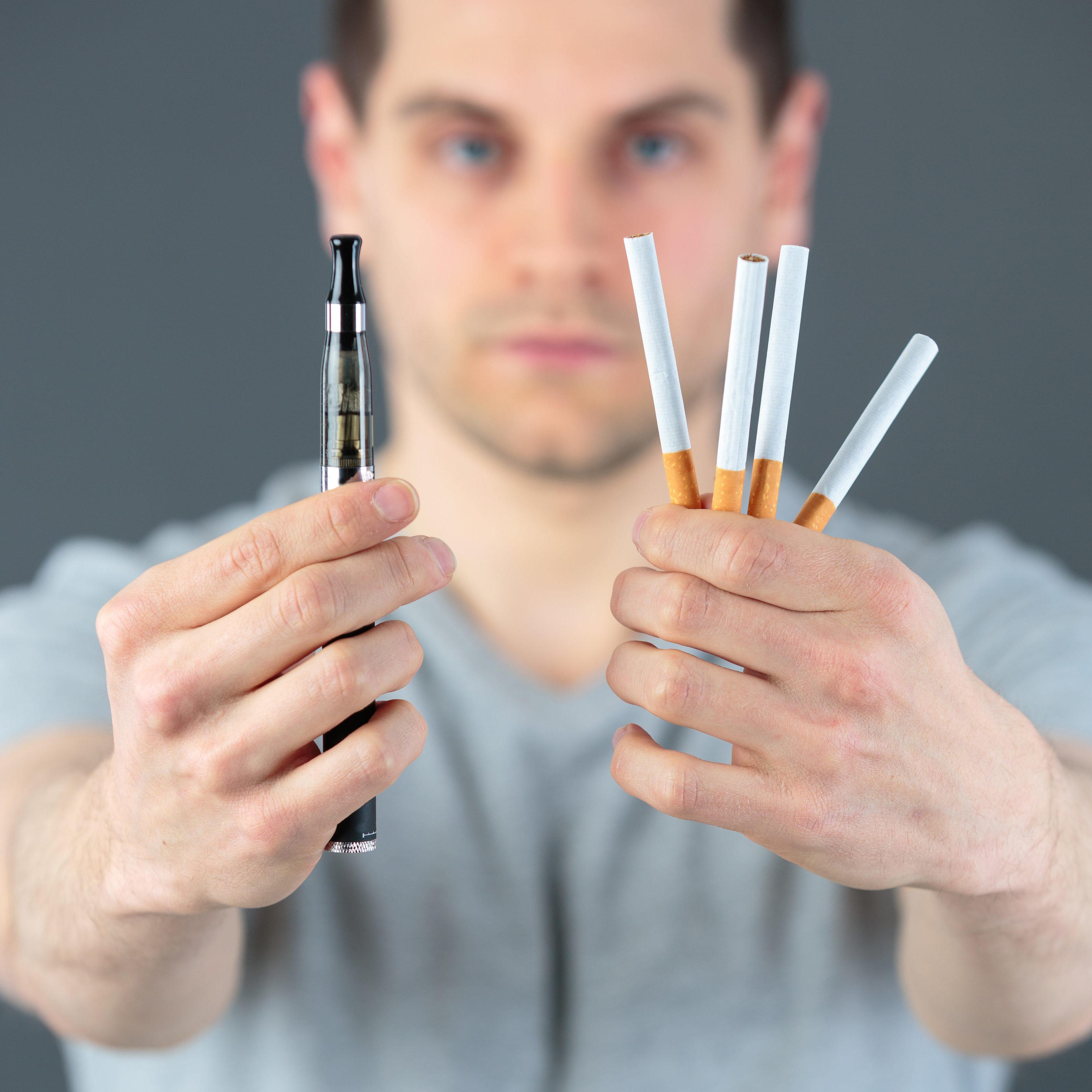 handsome man with e-cigarette and tobacco cigarette
